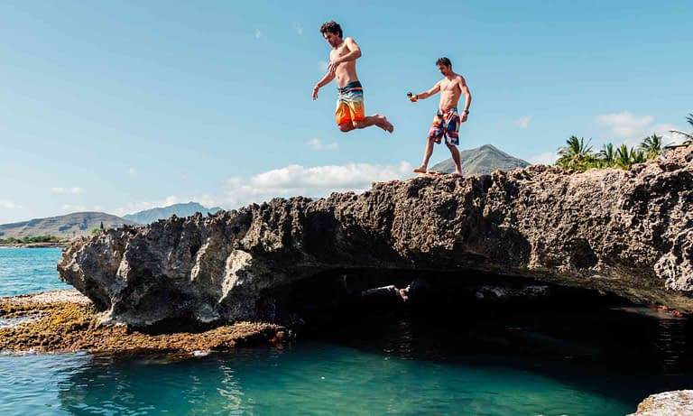 one man jumping off a cliff into the ocean on oahu